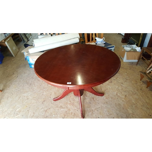 30 - A circular wooden breakfast/dining table mahogany-style on turned tripod base....