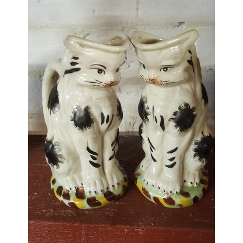 49 - A pair of porcelain decorative water jugs each in the form of a cat (2)...