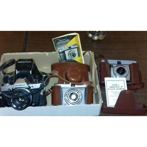 295 - 3 x vintage cameras in cases with manuals being Olympus OM10, Kodak Retinette and Mk 2 Coromatic 50...
