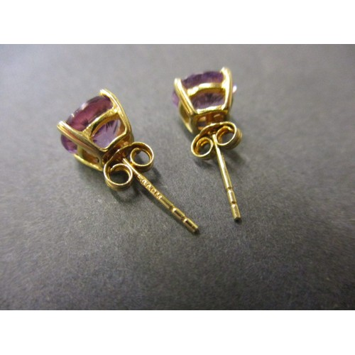 44 - A pair of 9ct gold and amethyst stud earrings, approx. size of stone 6.7mm across girdle, in good cl...