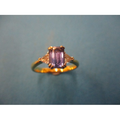 5 - An 18ct yellow and white gold ring with central emerald cut Tanzanite flanked by brilliant cut diamo...