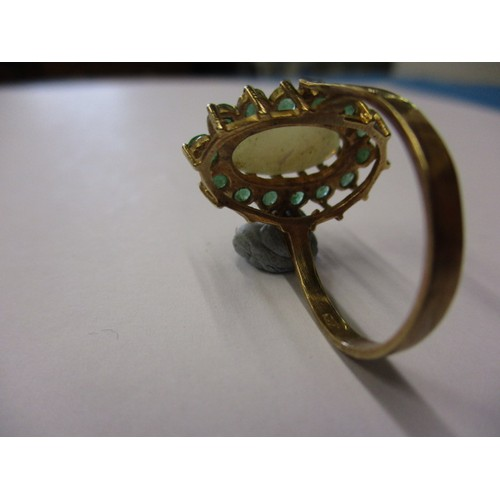 12 - A vintage 9ct yellow gold cocktail ring, set with a central cabochon opal surrounded by 14 emeralds?...