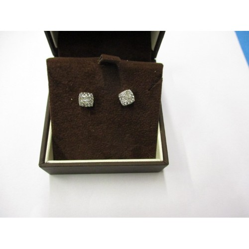 53 - A pair of 9ct white gold and diamond stud earrings, in good pre-owned condition with general age rel...