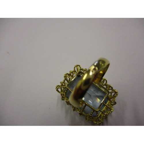 34 - A yellow gold ring marked 18k with a large pale blue topaz? set in a filigree mount, approx. ring si...