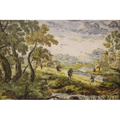 10 - A FRAMED 'CASTELLI' LANDSCAPE TILE WITH FIGURES AND BUILDINGS, possibly 18th century, inscribed vers...