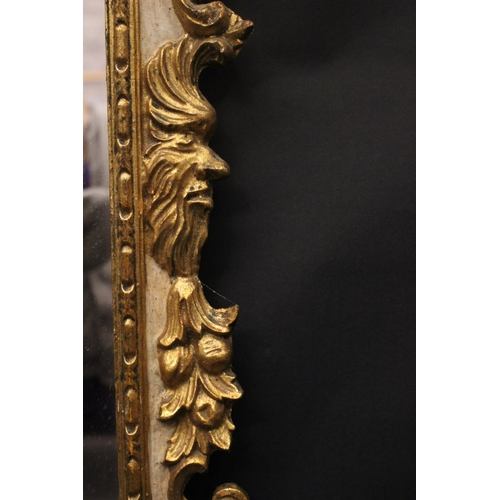 49 - A GILTWOOD WALL MIRROR, with winged cherub head pediment, faces & fruit branch decoration to the sid...