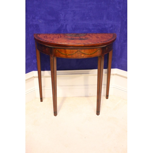 58 - A DEMI LUNE SATINWOOD FOLD OVER CARD TABLE, decorated with hand painted motif of foliage and cherubs...