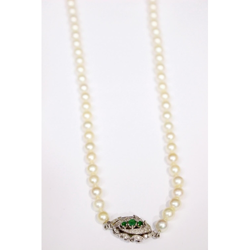 8 - A FRENCH PEARL NECKLACE, with platinum and gold clasp, encrusted with diamonds and 3 emeralds...