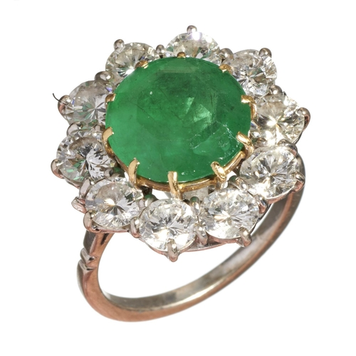 11 - <strong>AN EMERALD AND DIAMOND CLUSTER RING</strong> the emerald in a surround of ten round brilli...