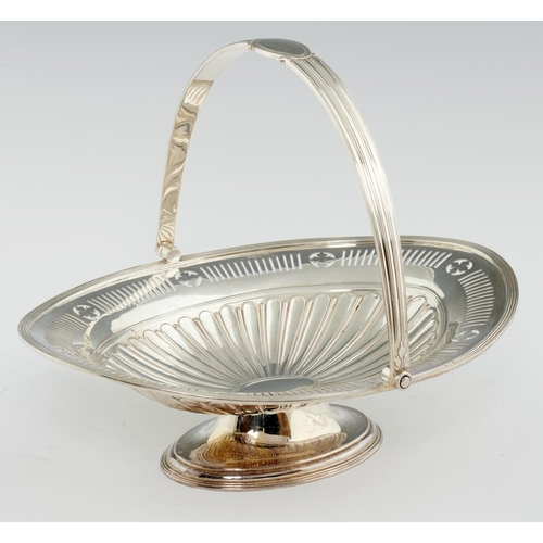 148 - <p>A GEORGE V NEO CLASSICAL STYLE PIERCED SILVER CAKE BASKET  with fluted swing handle, 23cm h, by L...