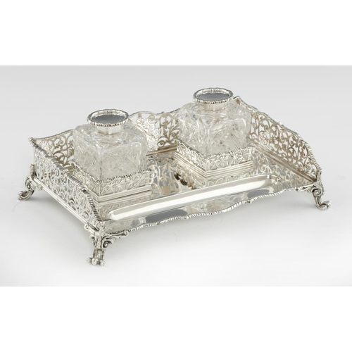 154 - <p>AN EDWARD VII GADROONED SILVER INKSTAND  with saw pierced galleries and pair of silver capped  cu...