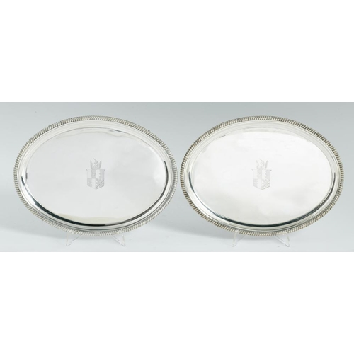 169 - <p>A PAIR OF GEORGE III OVAL SILVER WAITERS moulded cavetto and gadrooned rim, on four conforming fe...