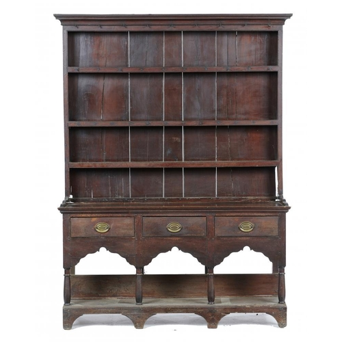 778 - <p>A GEORGE III OAK DRESSER  with cavetto cornice to the boarded three shelf rack, the base fitted t...