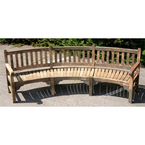 781 - <p>A CURVED TEAK GARDEN SEAT  with slightly dished, slatted seat, 99cm h, 300cm l</p><p></p>...