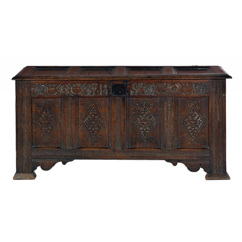 1097 - <p>A CHARLES II OAK CHEST, DATED 1675 with four-panel lid, the frieze carved with tulips flanked by ...