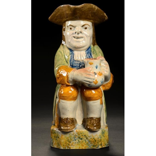 23 - <p>A STAFFORDSHIRE PRATTWARE TOBY JUG, EARLY 19TH C with sponged decoration to handle and base, bene...