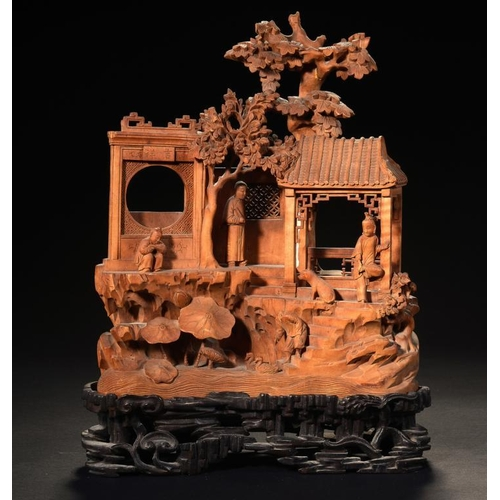 280 - <p>A CHINESE SANDALWOOD CARVING, 19TH C  of four figures in a pavilion beneath prunus on rocks, inco...