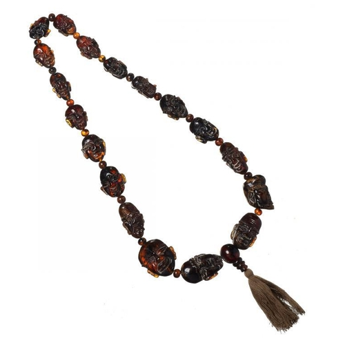 420 - <p>A NECKLACE OF 19 ROOT AMBER BEADS  carved as human heads, 103.9g</p>...