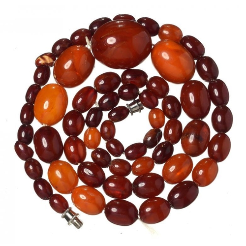 428 - <p>A NECKLACE OF 60 AMBER AND FATURAN BEADS 29.7g</p><p></p>...