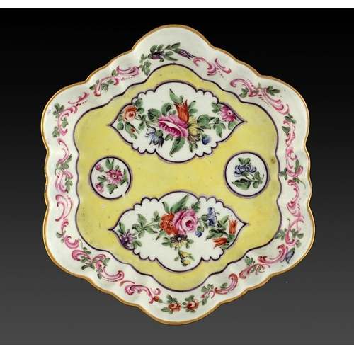 90 - <p>A WORCESTER TEAPOT STAND, THE PORCELAIN C1770  later enamelled with flowers on a yellow ground, 1...