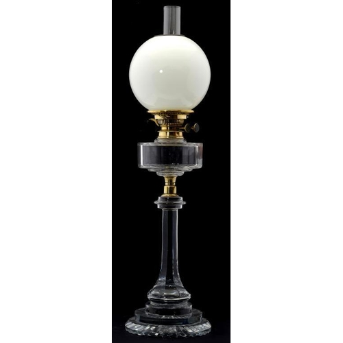 953 - <p>A VICTORIAN FACETED GLASS OIL LAMP, C1890  with brass collar and burner, on stepped star cut foot...