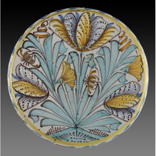 29 - <p>AN ENGLISH DELFTWARE BLUE DASH TULIP CHARGER, C1670-85  painted with tulips, lilies and carnation...