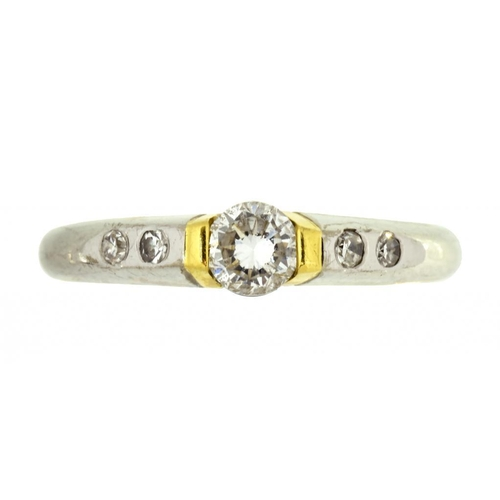 30 - <p>A DIAMOND RING the larger central round brilliant cut diamond in 18ct two colour gold, 4.2g, size...