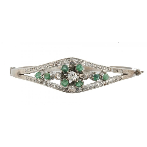 24 - <p>AN EMERALD AND DIAMOND BANGLE, the brilliant cut diamonds approx 0.6 ct, the emeralds approx 0.7 ...