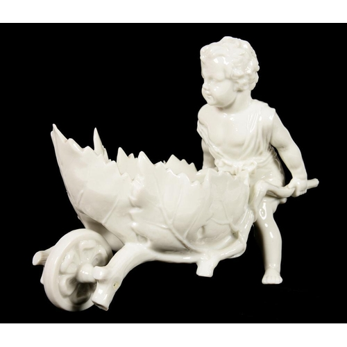 176 - <p>A CONTINENTAL GLAZED PORCELAIN FIGURE OF A CHILD PUSHING A RUSTIC WHEELBARROW, 14CM H, LATE 19TH ...