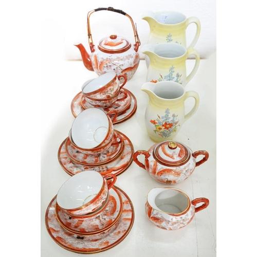 214 - <p>A JAPANESE EGGSHELL PORCELAIN TEA SERVICE AND A GRADUATED SET OF THREE NEWHALL EARTHENWARE JUGS, ...