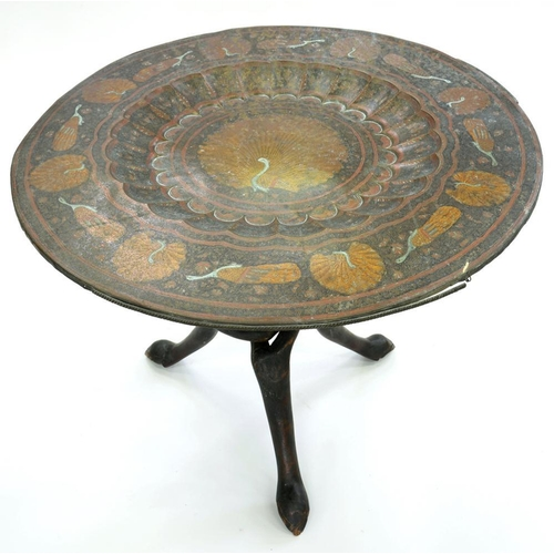 534 - <p>AN INDIAN PEACOCK DECORATED BRASS COFFEE TABLE ON CARVED AND STAINED WOOD ENTWINED LEGS, 75CM D, ...