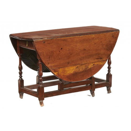 550 - <p>A GEORGE III WALNUT DROP LEAF TABLE, 18TH C, the oval top on baluster legs and gates, 71cm h; 119...