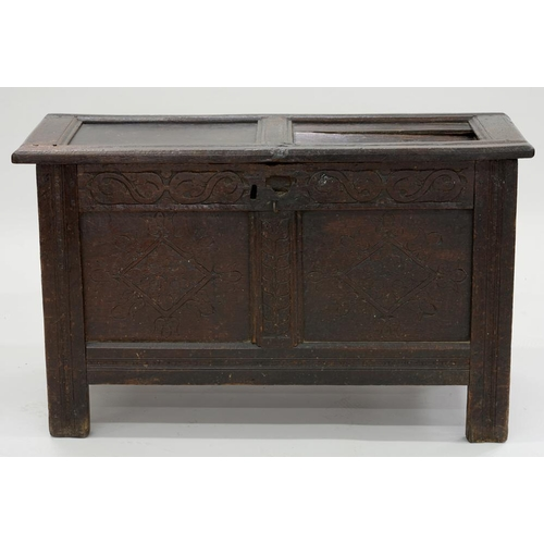 562 - <p>A CHARLES II OAK TWIN PANEL CHEST, THE FRONT CARVED WITH LOZENGES BENEATH S SCROLL FRIEZE, ON CHA...