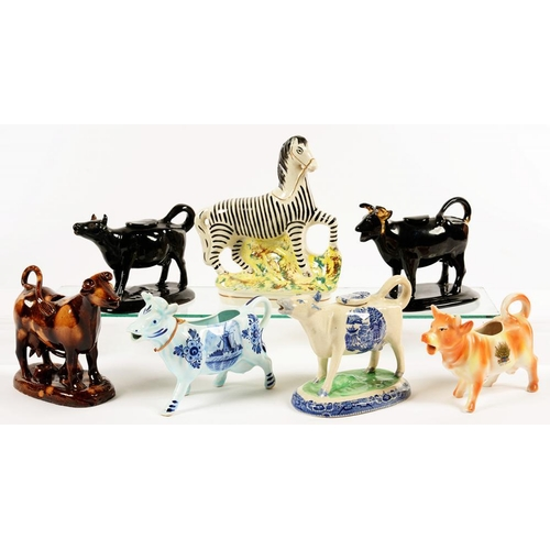 156 - <p>SIX ENGLISH AND CONTINTENTAL EARTHENWARE POTTERY AND PORCELAIN COW CREAMERS, VARIOUS SIZES, C1840...