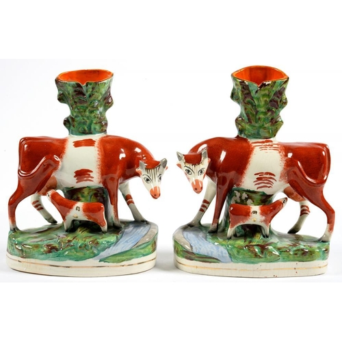 208 - <p>A PAIR OF STAFFORDSHIRE EARTHENWARE COW AND CALF SPILL HOLDER GROUPS, 27CM H, 19TH C, A SALTGLAZE...