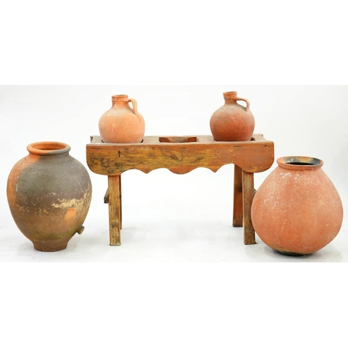 597 - <p>FOUR CONTINENTAL TERRACOTTA POTS AND A STAINED WOOD STAND, 60CM H; 109 X 36CM, EARLY 20TH C</p>...