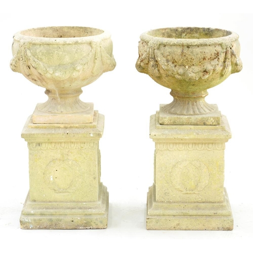 598 - <p>A PAIR OF RECONSTITUTED STONE VASES ON PLINTHS, 75CM H X 39CM </p>...