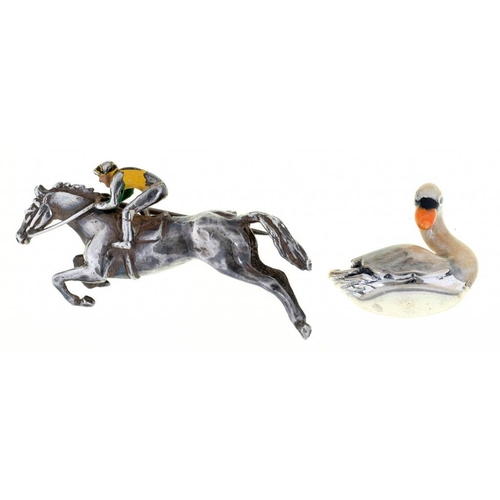42 - <p>A POLYCHROME DECORATED SILVER HORSE AND JOCKEY BROOCH AND A SILVER AND ENAMEL MINIATURE MODEL OF ...