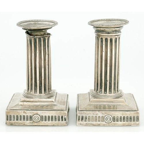 184 - <p>A PAIR OF VICTORIAN NEO-CLASSICAL STYLE SILVER DWARF COLUMNAR CANDLESTICKS, WITH NOZZLES, ON SQUA...