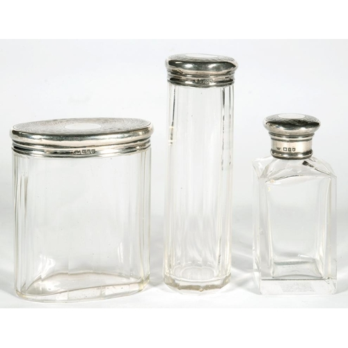 195 - <p>A SET OF THREE GEORGE V SILVER CAPPED CUT GLASS JARS / BOTTLES, VARIOUS SIZES, LONDON 1910 AND 19...