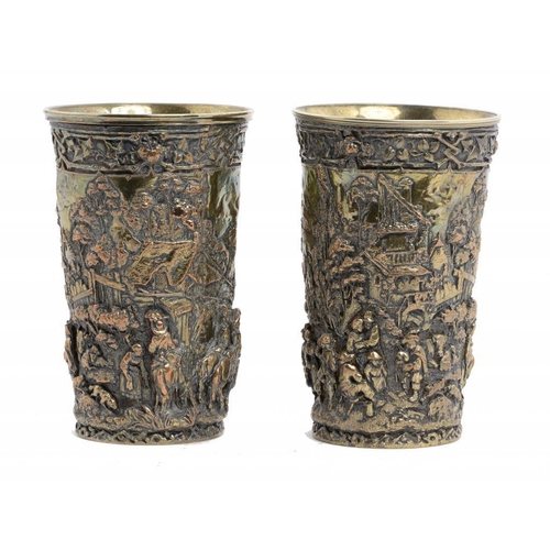 346 - <p>A PAIR OF SILVER PLATED COPPER ELECTROTYPE BEAKERS, LATE 19TH C, with continuous 'Teniers' scenes...