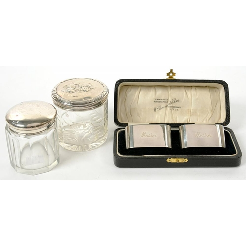 167 - <p>A PAIR OF GEORGE V SILVER NAPKIN RINGS, BIRMINGHAM 1933, CASED AND TWO SILVER TOPPED GLASS JARS, ...