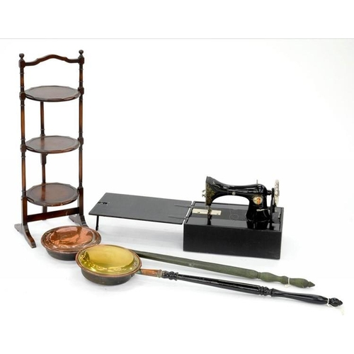 593 - <p>A MAHOGANY THREE TIER CAKE RACK, A TAILOR BIRD SEWING MACHINE AND TWO WARMING PANS</p>...