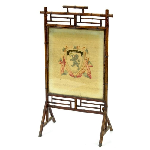 625 - <p>A BAMBOO FIRE SCREEN WITH WOOLWORK ARMORIAL PANEL OF EMMANUEL COLLEGE, 111CM H X 61CM W, EARLY 20...
