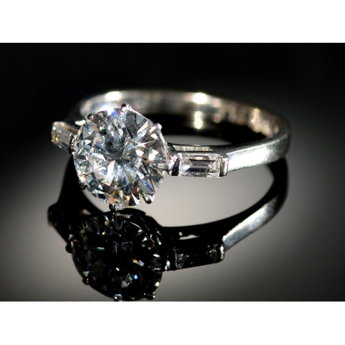 10 - <strong>A DIAMOND RING </strong> the round brilliant cut diamond of approx 2cts flanked by a baguett...