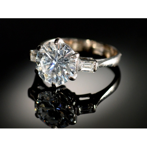 11 - <strong>A DIAMOND  RING</strong>   the round brilliant cut diamond of approx 3.2cts flanked by a bag...