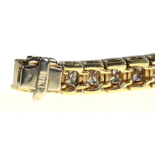 13 - <strong>A DIAMOND LINE BRACELET </strong>withprincess cut diamonds of approx 10ct in total, in gold...