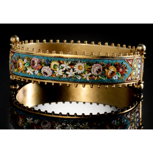 52 - <strong>AN ITALIAN SILVER GILT AND MICROMOSAIC BANGLE, C1870 </strong> one side decorated with birds...