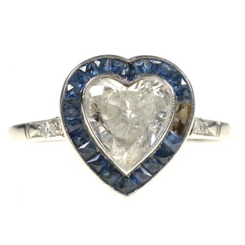 6 - <strong>A HEART SHAPED DIAMOND AND SAPPHIRE CLUSTER RING </strong>with surround of calibre cut sapph...