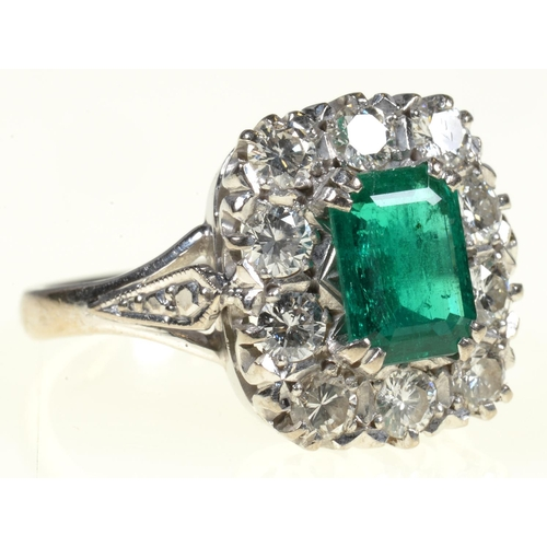 8 - <strong>AN EMERALD AND DIAMOND RING </strong> the step cut emerald of approx 4 x 6mm in a surround o...